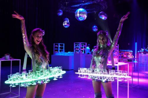 Champagne Dames met Disco look in de Spiegeljurk. Gastenontvangst, 80 - 90 Party, Mirrorball, Champagne displays, Thema events, food entertainment, Luxe catering act, Champagne Girls, Disco Girls.