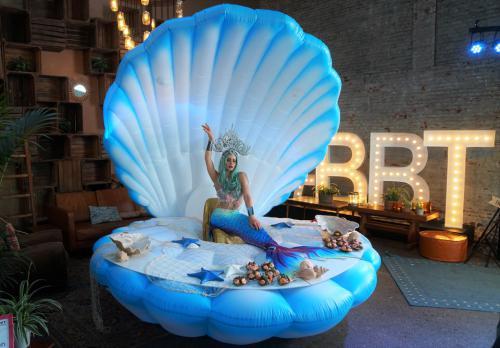 Het Ocean Mermaid themakostuum in combinatie met het Themadames Ocean Decor in functie van LED food bar bij buffet van BBT Online Event. Zeemeermin, Foodbar, Seafood, food entertainment, LED zeeschelp, Ocean Events, Summer festivals.